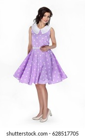 Charming girl in purple dress with polka dots turns around looking at camera on white background