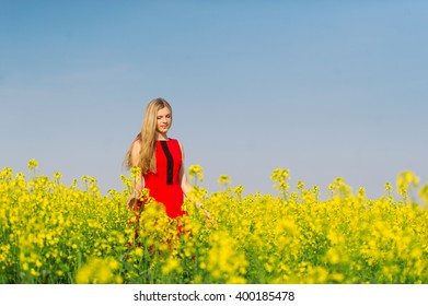 The charming girl in red is on the yellow rape field.