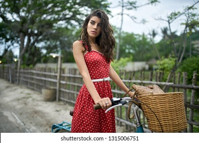Charming girl in red polka dot dress stands with a blue bike on the dirt road on the background of the wooden fence and tropical trees and the sky. She looks to the side with parted lips. Horizontal.