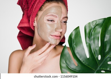 charming girl with a red towel on her head applies a useful clay mask to half the face