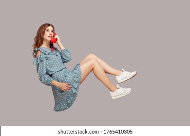 Charming girl in ruffle dress holding phone handset levitating, hovering floating air and having conversation on telephone, looking up with dreamy expression. studio shot isolated gray background,
