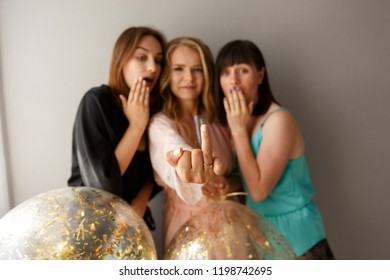 Charming girl showing an engagement ring on the finger, celebrating the bridal shower with girls in silk pajamas. Hen-party at home.