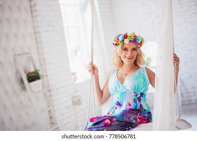 The charming girl sits on the swing