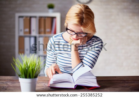Charming girl sitting by wooden table and reading book