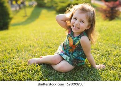 charming girl sitting on grass in sunlight