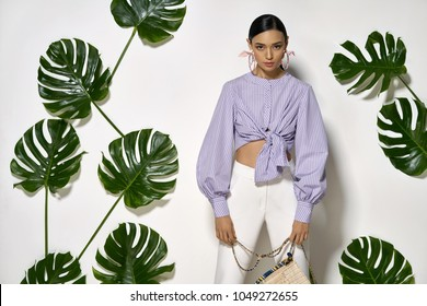 Charming girl with a straw bag is posing in a studio on a background of a white wall with big green leaves. She wears a striped lilac shirt, white pants and big colorful earrings. Horizontal.