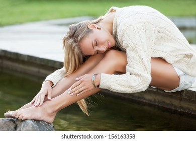 Charming girl in sweater near the water