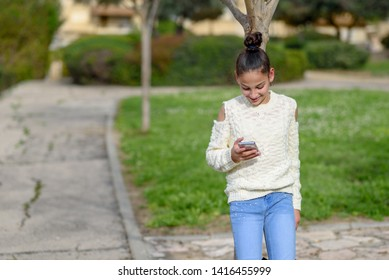 Charming girl young blogger with beautiful smile reading good news on mobile phone. Happy female watching her photos on cell telephone while relaxing in nature during free time.