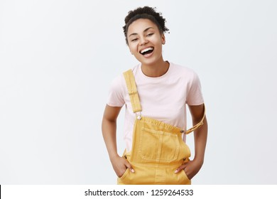 Charming girlfriend with dark skin and curly hair laughing out loud, wearing cute yellow overalls with strap falling on arm, holding hands in pocket and smiling joyfully while talking with boyfriend
