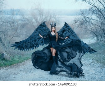 charming gorgeous dark goddess controls wind, air flow waves hem and long train of light black dress with wide lace sleeves, lady with sharp horns and black feather wings ready to fly into sky