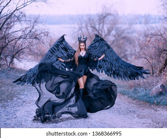 charming gorgeous dark witch controls power wind waves silk fabric hem long train black dress gothic queen horns feather wings fly. Maleficent  purple color nature backdrop spring autumn tree bare