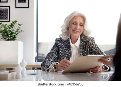Charming gray-haired lady is expressing gladness