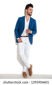 Charming guy romantically looking to the side and holding one of his hand in his pocket while wearing a blue suit and leaning on white studio background