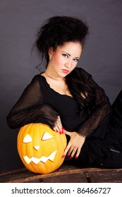 Charming halloween witch with pumpkin