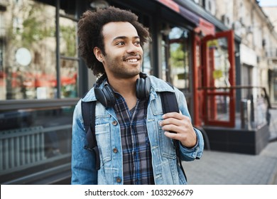 Charming handsome african-american male with bristle and afro haircut looking aside while holding backpack and strolling in city. DJ heading to club to perform his new tracks