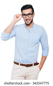Charming handsome. Confident young Indian man adjusting his eyeglasses and smiling while standing against white background
