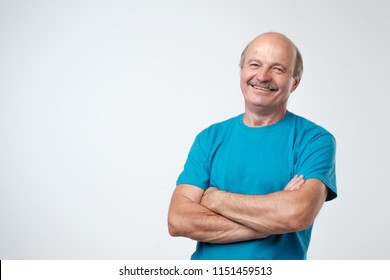 Charming handsome senior man in casual clothes keeping arms crossed and smiling while standing isolated on white background.