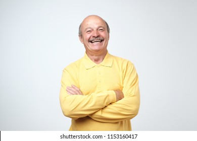 Charming handsome senior man in casual clothes keeping arms crossed and laughing while standing isolated on white background.