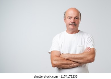 Charming handsome senior man in casual clothes keeping arms crossed and smiling while standing isolated on white background. Positive facial emotion