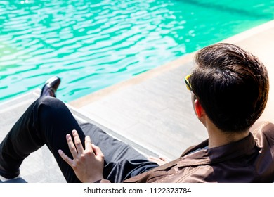 Charming handsome young businessman sits near swimming pool for taking a rest after work that makes him feeling good, relaxed and comfortable. Cool guy gets fresh air outside his office. copy space