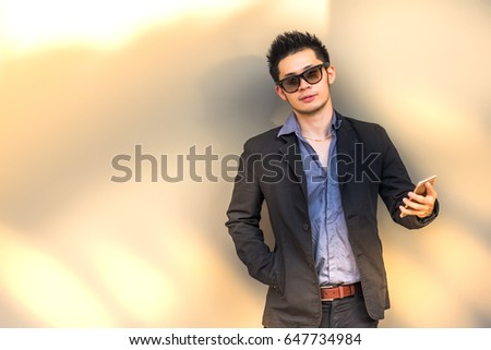 9cb607d09a1 Charming handsome young man or attractive handsome businessman is holding  smart phone. Cool guy wears