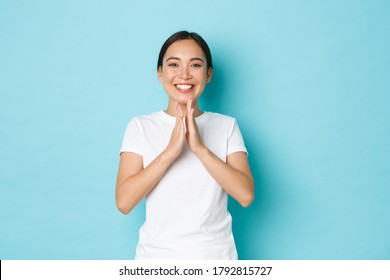 Charming happy asian female in white t-shrit smiling satisfied, clapping hands, congratulate person with win, praising good work, well done, compliment someone achievement, blue background
