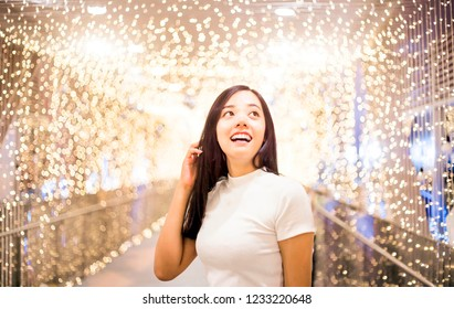 charming happy  asian lady in casual suite post on night light decoration at holiday. fashion wearing to party at night.