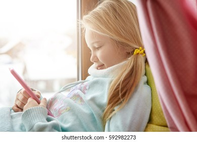 Charming happy blonde female child with messy ponytail using wireless internet connection on smart phone at home, enjoying online communication, messaging friends, sitting on windowsill alone