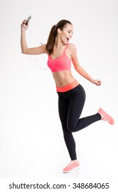 Charming happy young fitness woman in sportwear listening to music from mobile phone and dancing over white background
