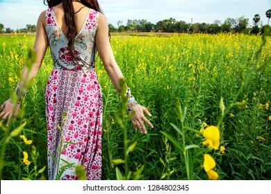 Charmanter Hippie-Lifestyle für Mädchen. Schöne, sorgenfreie Frau auf den Feldern, die sich im Natursommer glücklich und offen die Hände im Freien bei Sonnenuntergang öffnet. Schöne Mädchen in böhmischen Kleid auf Blume. Glückliche Frau zu Fuß.