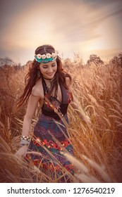 Charming Hippie girl  lifestyle concept. Beautiful carefree woman in fields being happy outdoors. Portrait of a beautiful girls in a Bohemian dress in grass flower field with ears at sunset in summer
