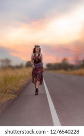 Charming Hippie girl  lifestyle concept. Beautiful carefree woman in fields being happy outdoors. Portrait of a beautiful girls in a Bohemian dress walking on Highways street road at sunset in summer.