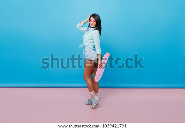 Charming hispanic woman with straight black hair standing on tip-toe and holding pink skateboard. Place for text.Indoor photo of pretty asian female model in sunglasses wears sport shoes and denim