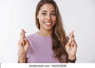 Charming hopeful girlfriend keeping high hopes cross fingers good luck smiling broadly anticipating dream come true, standing excited awaiting good results, praying white background