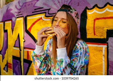 Charming hungry woman, enjoying eating a burger, closed her eyes. Dressed in stylish jacket and cap, in sunglasses. Standing against the wall with graffiti, outdoors.