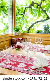 A charming and inviting restaurnt table with a bay window and grapevines behind with colorful place settings