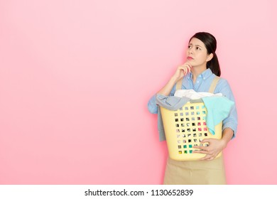 charming Japanese housewife question thinking and holding a basket of clothing