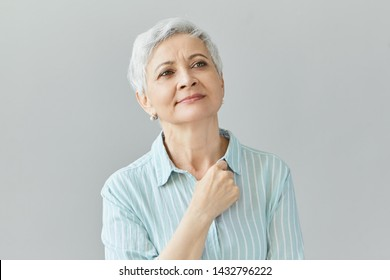 Charming joyful female pensioner wearing stylish clothes holding hand at her chest, looking up, having nostalgia for old times, reminiscing, daydreaming, having dreamy pleased facial expression
