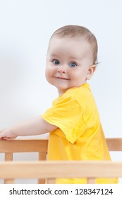 Charming kid in the crib. Baby girl in yellow looking at camera