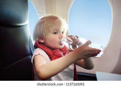 Charming kid traveling by an airplane. Little boy drinking water during the flight. Air travel with little kids