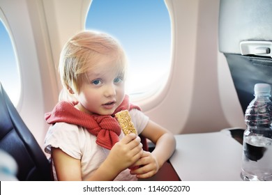 Charming kid traveling by an airplane. Little boy drinking water and eating snack during the flight. Air travel with little kids