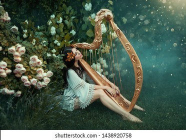 charming lady with dark black hair sits on the frozen grass alone with light white fog, forest nymph with haze plays harp, girl in simple shirt and with bare legs near rose bush, creative photo