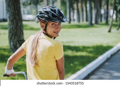 Charming lady on bike looking at camera and smiling