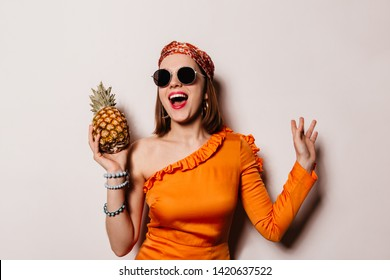 Charming lady in orange blouse, headdress and glasses laughs and holds pineapple on white background