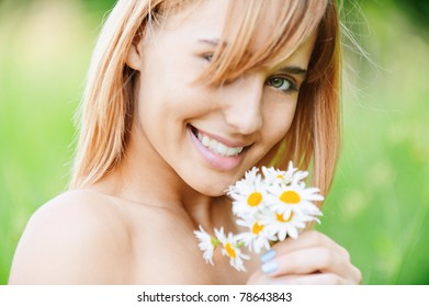 Charming laughing young woman with bouquet of camomiles, on green summer background.