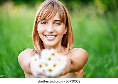 Charming laughing young woman gives bouquet of camomiles, on green summer background.