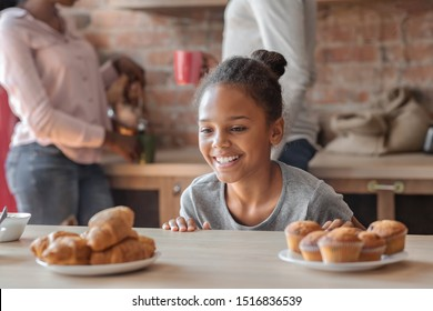 Charming little african girl looking with joy at sweets while parents busy, kitchen interior, copy space