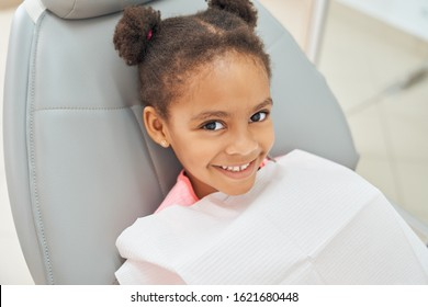 Charming little afro american girl sitting in dental chair smiling and looking at camera. Little female patient waiting for dental treatment at modern clinic.