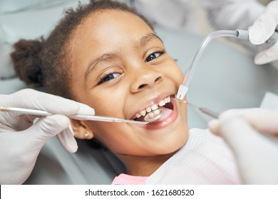 Charming little afro american girl sitting in dental chair, smiling and looking at camera during medical treatment at modern clinic. Concept of health care ad pediatrics