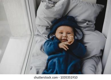 Charming little boy in blue suit looks like a bear lying on grey blanket before a window